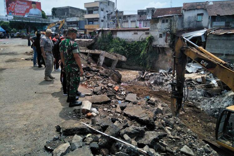 Material bangunan kompleks pertokoan jompo yang ambruk menutup sungai, mulai dibersihkan, Selasa (3/3/2020).