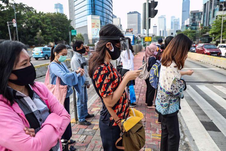 Pekerja yang menggunakan masker saat menunggu menyebrangi zebra cross di Jalan M.H Thamrin, Jakarta Pusat, Senin (14/9/2020). PSBB kembali diterapkan tanggal 14 September 2020, berbagai aktivitas kembali dibatasi yakni aktivitas perkantoran, usaha, transportasi, hingga fasilitas umum.