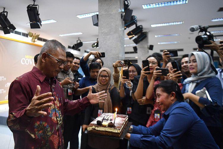Juru bicara pemerintah untuk penanganan COVID-19 Achmad Yurianto (kiri) menerima kue ulang tahun seusai memberikan keterangan pers di Kantor Presiden, Jakarta, Rabu (11/3/2020). Pemerintah menyatakan hingga Rabu (11/3) sore pasien positif COVID-19 di Indonesia bertambah dari 27 menjadi 34.