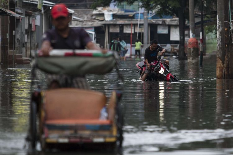 Sejumlah warga terjatuh saat melintasi jalan yang tergenang banjir di wilayah Teluk Gong, Penjaringan, Jakarta Utara, Sabtu (4/1/2020).Hujan lebat di awal tahun membuat kawasan teluk gong masih terendam banjir.