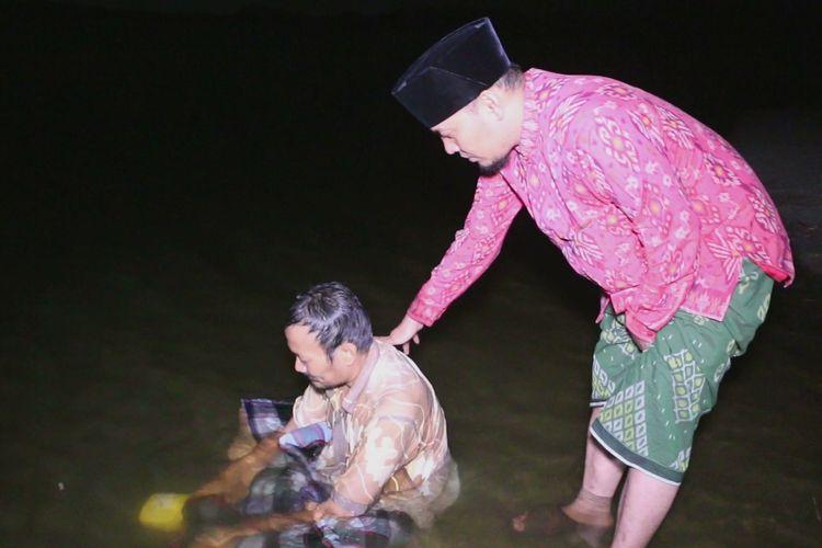 Ustaz Ujang Bushtomi pemilik Padepokan Anti Galau memandikan Mursyid (45) di Waduk Setupatok, Selasa malam (24/4/2019). Mursyid adalah tim sukses calon anggota DPRD Kabupaten Cirebon yang depresi karena tertekan perolehan suara yang kecil.