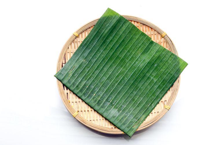 Ilustrasi daun pisang di atas wadah bambu.