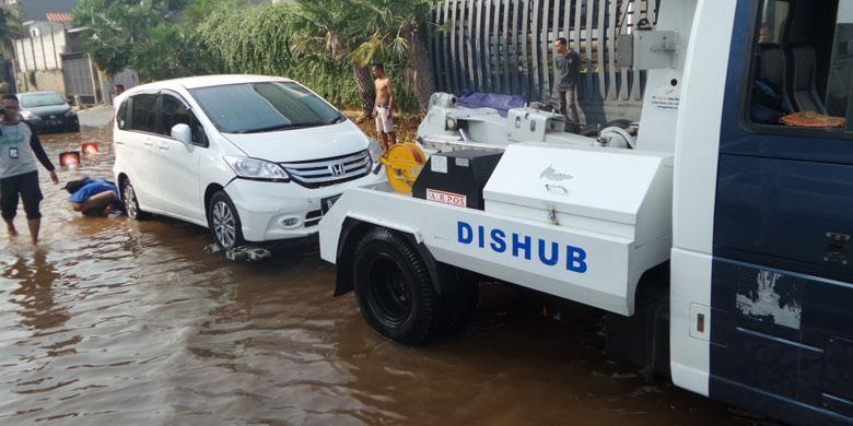 Mobil derek Dinas Perhubungan DKI Jakarta, Sabtu (4/6/2016), menarik mobil milik warga yang terendam banjir akibat tanggul jebol di Pantai Mutiara, Penjaringan, Jakarta Utara, pada Jumat malam sebelumnya.