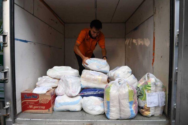 Petugas mengumpulkan barang belanjaan dari Lumbung Pangan Jatim untuk dikirim ke Gresik dan Sidoarjo.