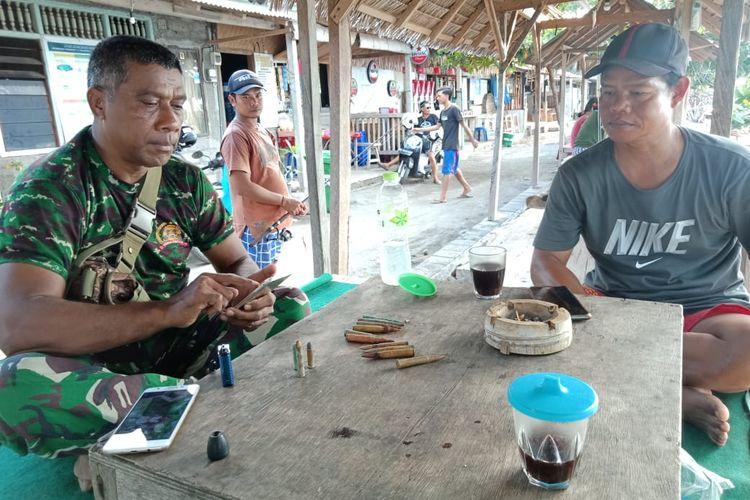 Warga menyerahkan peluru hasil temuannya ke anggota TNI.