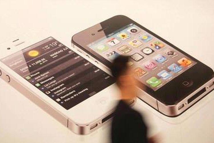 Pengunjung melintas di depan gambar produk baru Apple Inc yaitu iPhone 4S pada penjualan perdana oleh Telkomsel di Jakarta, Jumat (27/1/2012). Telepon pintar tersebut dijual pada kisaran Rp 7-10 juta, tergantung kapasitas dan operatornya. KOMPAS/PRIYOMBODO