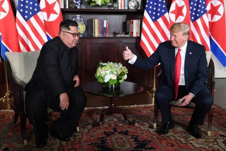Presiden Amerika Serikat Donald Trump dan pemimpin Korea Utara Kim Jong Un duduk bersebelahan untuk menyapa media di Hotel Capella, Singapura, Selasa (12/6/2018). (AFP/Saul Loeb)