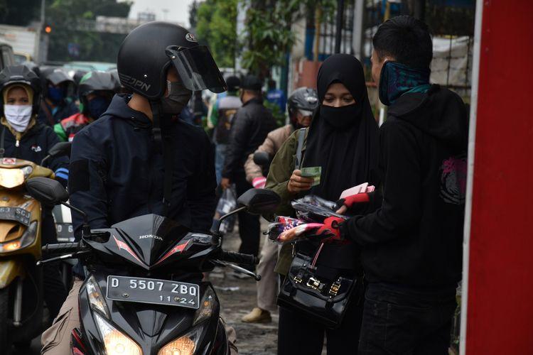 Sejumlah warga menjajakan dagangannya berupa masker dan sarung tangan di pinggir jalan sebelum pemeriksaan petugas di Check Point saat PSBB Jabar diberlakukan, Rabu (6/5/2020).