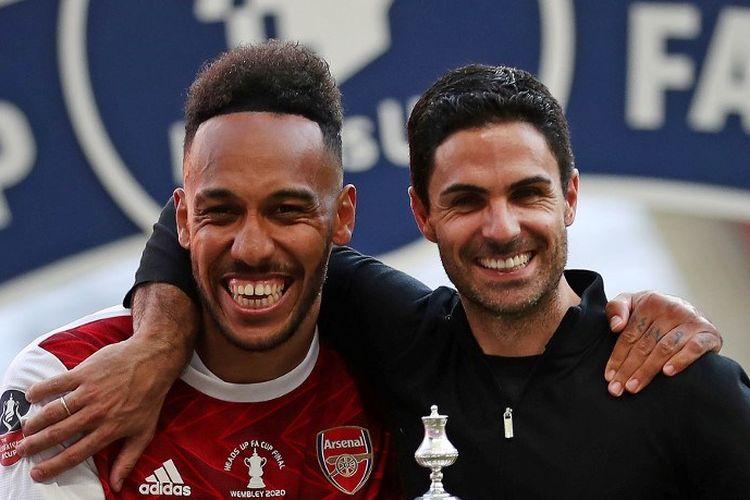 Penyerang Arsenal, Pierre-Emerick Aubameyang (kiri), bersama sang pelatih Mikel Arteta (kanan) saat merayakan trofi Piala FA 2019-2020.