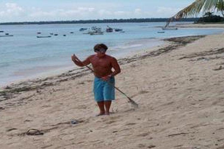 Paul Rainbow (45), turis asal Australia, menyapu pantai Nemberala, Rote Ndao, NTT, Jumat (18/5/2013). Kegiatan ini dilakukan setiap sore hari, saat pantai itu kotor. Penduduk lokal tak peduli terhadap kebersihan pantai itu,