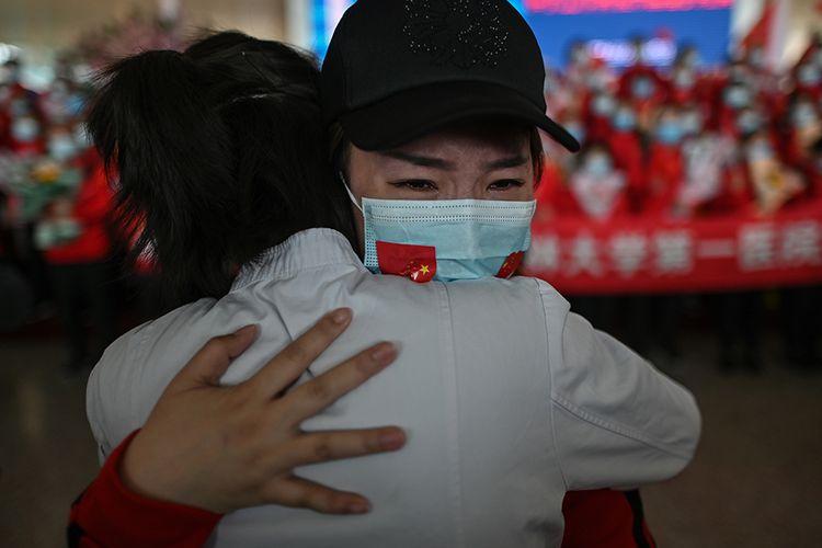 Seorang petugas medis dari Provinsi Jilin (kanan) menangis saat memeluk rekan perawat yang bersama-sama selama menangani pasien corona, dalam sebuah acara perpisahan di Bandara Tianhe yang baru dibuka kembali di Wuhan, Hubei, China, Rabu (8/4/2020). Ribuan orang bergegas meninggalkan Wuhan setelah otoritas mencabut kebijakan lockdown selama lebih dari dua bulan di lokasi yang diketahui sebagai episenter awal virus corona tersebut.