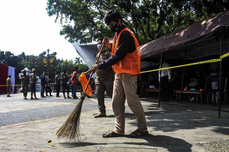 Pelanggar protokol kesehatan yang tertangkap tak menggunakan masker oleh Satgas Covid-19 diberikan sanksi sosial untuk membersihkan rumput dan daun di pelataran Monumen Perjuangan Rakyat (Monpera) Palembang, Sumatera Selatan, Kamis (17/9/2020).
