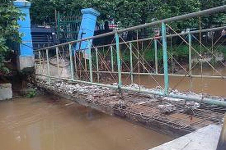 Jembatan yang menghubungkan Kelurahan Tengah dan Jalan Raya Bogor di atas Kali Baru, Kecamatan Kramat Jati, Jakarta Timur, ambles akibat turap di tepi sungai tersebut ambrol pada Selasa (21/1/2014) malam.