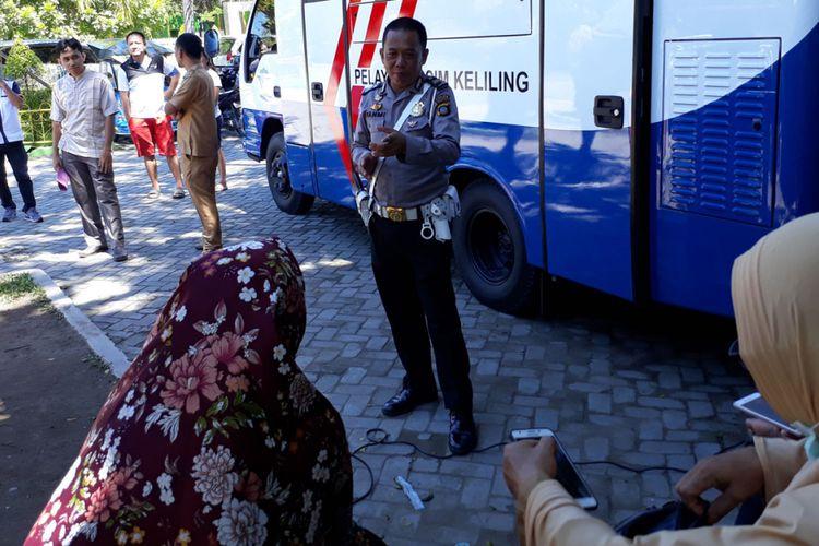 Aiptu Ramdan Fahmi saat berbagi ilmu dengan warga Gorontalo yang mengantre layanan perpanjangan SIM di Taman Kota, Kota Gorontalo.