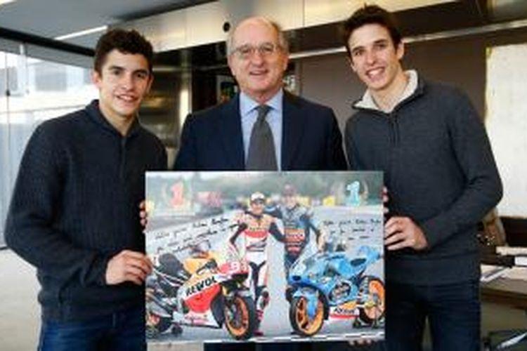 Pebalap Repsol Honda asal Spanyol, Marc Marquez (kiri), dan adiknya, Alex Marquez (kanan), menerima penghargaan dari bos Repsol, Antonio Brufau, di Madrid.