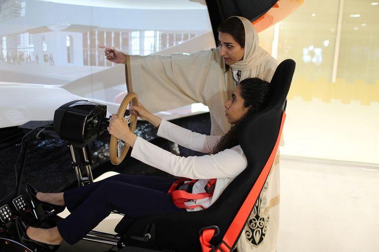 A driving instructor (back) teaches trainee Maria al-Faraj during a driving lesson on a 3D screen at Saudi Aramco Driving Center in Dhahran, Saudi Arabia, June 6, 2018. REUTERS/Ahmed Jadallah