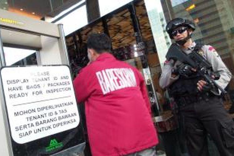 Personel Brimob tengah berjaga di pintu masuk Menara Mulia, Jakarta Selatan, Selasa (5/5/2015). Penyidik Direktorat Tindak Pidana Ekonomi dan Khusus tengah menggeledah ruangan milik SKK Migas terkait perkara dugaan korupsi.