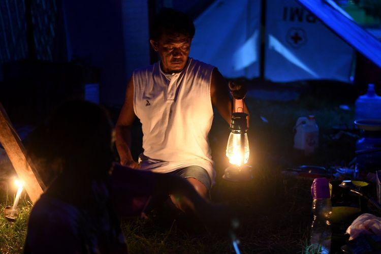 Warga membawa lampu petromaks untuk penerangan di tenda pengungsian kawasan Palu Barat, Senin (8/10). Berdasarkan data BNPB mengungsi akibat gempa dan tsunami Palu sebanyak 74.444 warga di 147 titik lokasi pengungsian.