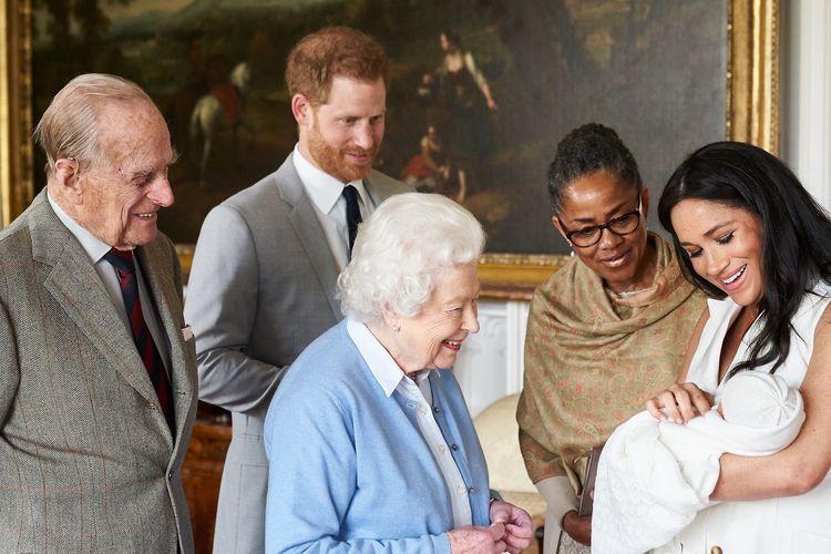 Sebuah foto yang dirilis Duke dan Duchess of Sussex pada 8 Mei 2019 memperlihatkan Pangeran Philip (kiri), Ratu Elizabeth, Pangeran Harry, Meghan Markle dan ibunya Doria Ragland memandangi bayi Meghan yang diberi nama Archie Harrison Mountbatten-Windsor.