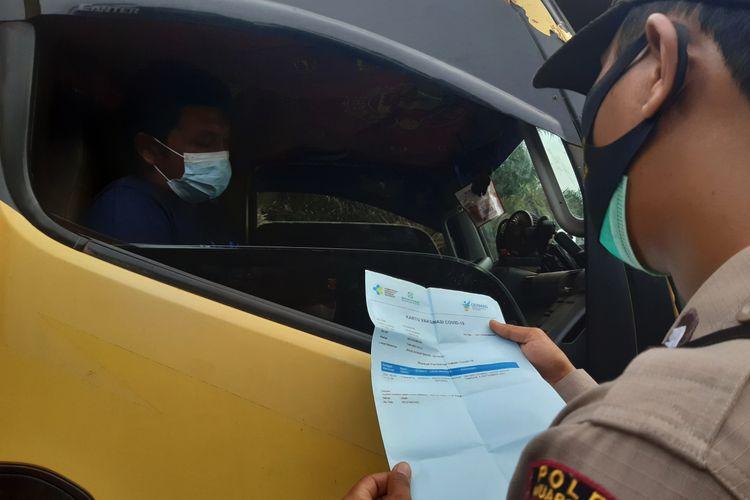 Salah satu petugas memeriksa surat vaksin yang dimiliki supir truk saat melewati oenyekatan di wikayah Bahar Utara Kabupaten Muaro Jambi, pada Kamis (12/8/2021).