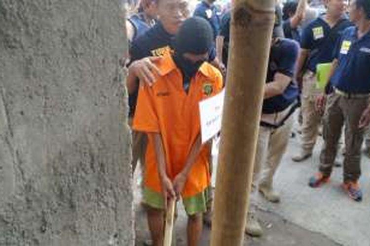 Tersangka pembunuh EF (19) yang masih di bawah umur, RA (16), memperagakan adegan mengambil pacul sebagai alat pembunuhan dalam rekonstruksi di mes karyawan PT Polyta Global Mandiri, Kosambi, Kabupaten Tangerang, Selasa (17/5/2016).