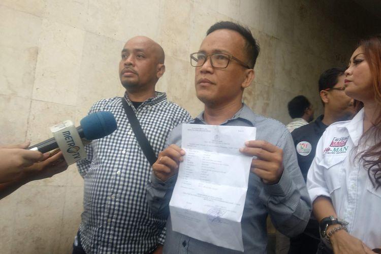 Ketua Umum Tim Jokowi Mania Immanuel Ebenezer menunjukkan laporan terhadap perempuan perekam video seorang pria yang mengancam memenggal Presiden Joko Widodo, di Mapolda Metro Jaya, Minggu (12/5/2019).