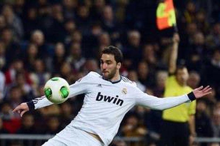 Penyerang Real Madrid dari Argentina, Gonzalo Higuain, menyepak bola dalam laga pertama Copa del Rey melawan Barcelona di Stadion Santiago Bernabeu, Rabu (30/1/2013). Pertandingan itu berakhir 1-1.