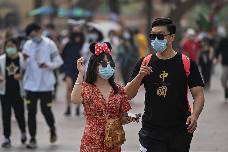 Pengunjung mengenakan masker saat mendatangi taman hiburan Disneyland, Shanghai, China, yang baru dibuka kembali, Senin (11/5/2020). Shanghai Disneyland resmi kembali dibuka setelah ditutup selama 4 bulan akibat pandemi virus corona.