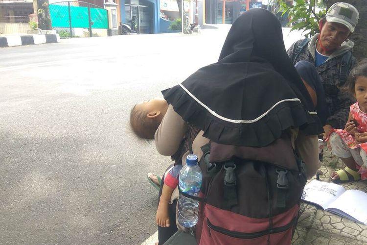Dani dan keluarga sedang melepas lelah di trotoar jalan nasional di Kabupaten Ciamis, Jumat (7/5/2021).