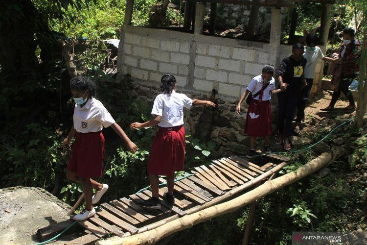 Sejumlah murid dengan hati-hati menyeberangi jembatan darurat ketika hendak berangkat ke sekolah di Kecamatan Alak, Kota Kupang, Kamis (18/3/2021)