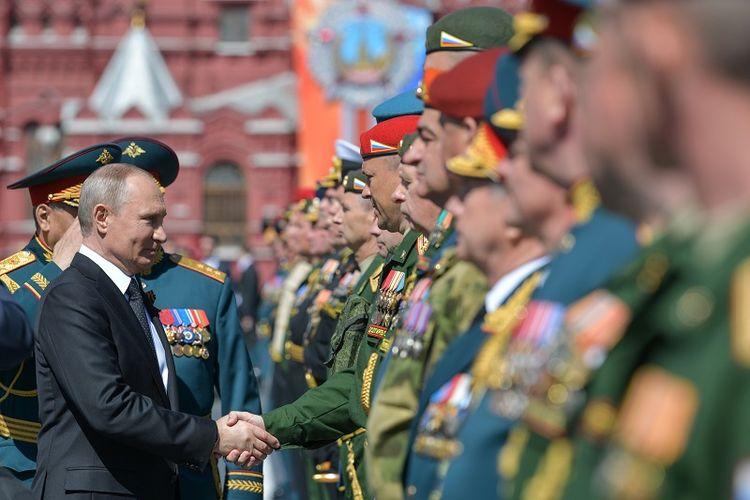 Presiden Rusia Vladimir Putin menjabat tangan para veteran dan personel militer dalam parade Victory Day di Lapangan Merah, Moskwa, Rabu (9/5/2018).
