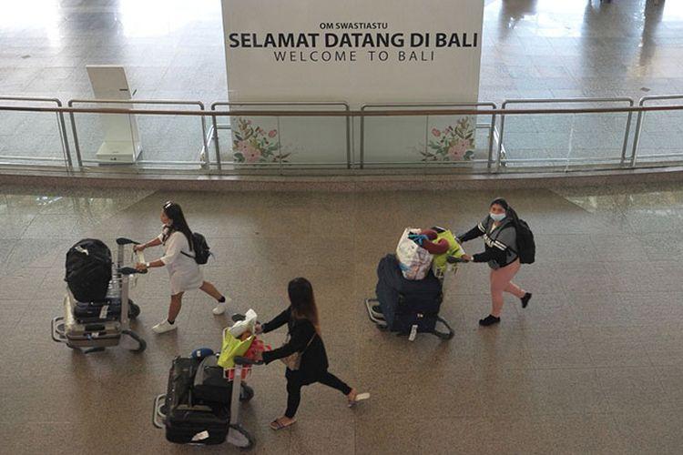 Penumpang pesawat membawa barang bawaannya di Terminal Kedatangan Internasional Bandara Internasional I Gusti Ngurah Rai Bali, Jumat (20/3/2020). Sebanyak 181.053 orang penumpang rute internasional tercatat tiba di bandara tersebut pada periode 1-19 Maret 2020, atau mengalami penurunan 40,2 persen jika dibandingkan catatan periode yang sama pada tahun 2019 yaitu sebesar 302.914 orang penumpang.