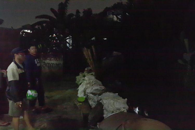 Warga sedang membersihkan lumpur sisa banjir.
