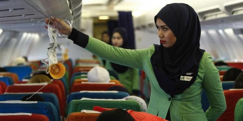 Dalam foto bertanggal 22 Desember 2015, seorang pramugari Rayani Air tengah menyiapkan kesiapan kabin sebelum penerbangan dari bandara Sultan Ismail Petra, di Kelantan, Malaysia.