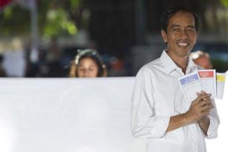 Calon presiden dari Partai Demokrasi Indonesia Perjuangan (PDI-P), Joko Widodo, menunjukkan surat suara usai mencoblos di TPS 27, Taman Menteng, Jakarta Pusat, Rabu (9/4/2014). Pada hari ini warga Indonesia melakukan pemilihan umum untuk memilih anggota legislatif periode 2014-2019.