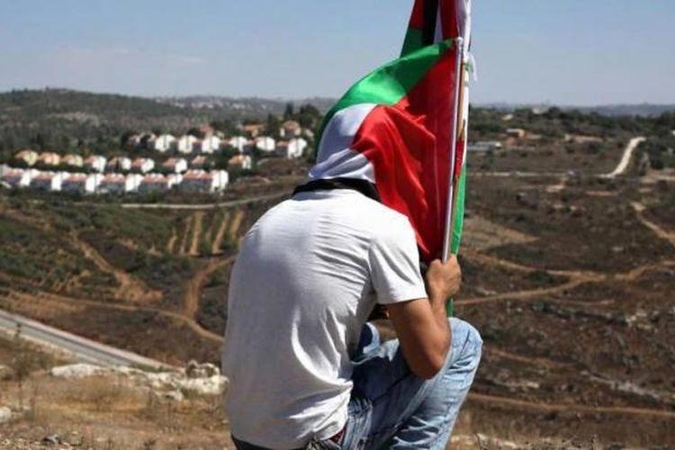 Seorang demonstranduduk sambil memegang bendera Palestina setelah aksi melawan perampasan tanah Palestina untuk memperluas pemukiman Yahudi Hallamish (latar belakang), Jumat (28/8/2015), di Desa Nabi Saleh, Tepi Barat, dekat Ramallah.