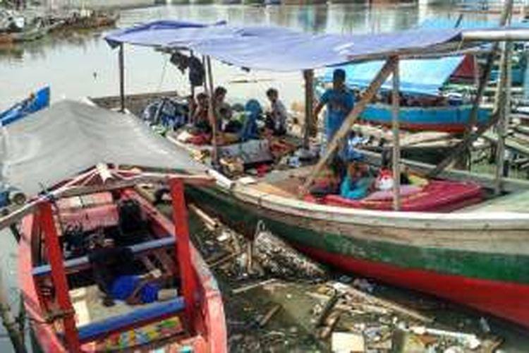 Warga Pasar Ikan, Penjaringan, Jakarta Utara, tampak duduk-duduk dan tidur di perahu, Jumat (15/4/2016) siang.