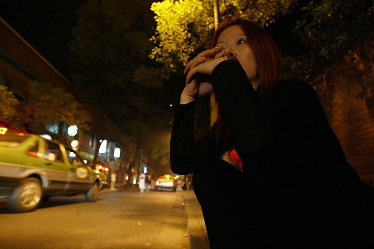 Seorang pekerja seks komersial (PSK) duduk dalam kegelapan saat  menunggu pelanggan di dekat sebuah distrik bar populer di Shanghai, China, pada 7 Juni 2003.