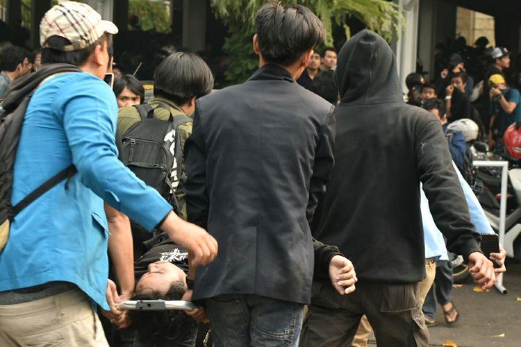 Aksi massa unjuk rasa di Gedung DPRD Jabar, Kota Bandung berakhir ricuh, Selasa (24/9/2019). Terlihat massa tengah menggotong rekannya yang terkulai lemas setelah menghirup gas air mata.