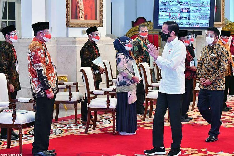 Presiden Joko Widodo (Jokowi) menyerahkan secara simbolis sertifikat hak atas tanah kepada masyarakat melalui program Sertifikat Tanah untuk Rakyat Seindonesia di Istana Negara, Jakarta, Senin (5/1/2021). Hari ini, Presiden menyerahkan 584.407 sertifikat tanah di 26 provinsi dan 273 kabupaten/kota sebagai bentuk komitmen Pemerintah untuk terus mempercepat penyertifikatan tanah di seluruh Indonesia.