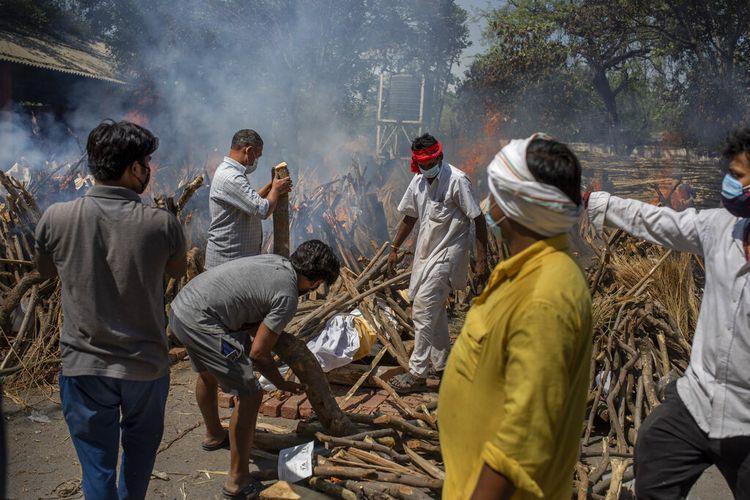 Anggota keluarga korban Covid-19 menyiapkan tumpukan kayu pemakaman untuk anggota yang meninggal di krematorium di New Delhi, India.