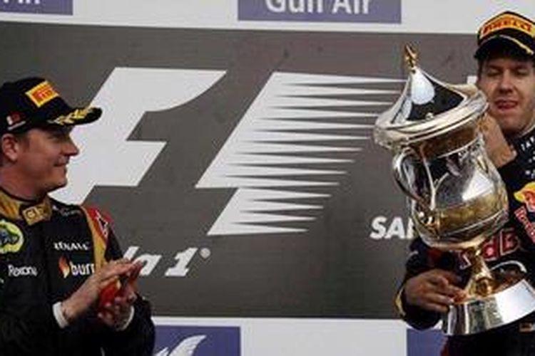 Pebalap Lotus, Kimi Raikkonen (kiri), dan pebalap Red Bull Racing, Sebastian Vettel, di atas podium GP Bahrain, Minggu (21/4/2013). Vettel memenangi balapan ini, Raikkonen runner-up.