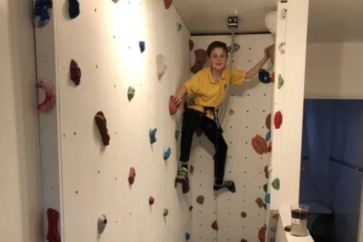 Eddie mencoba dinding panjat yang dibuat oleh ayahnya di rumah.