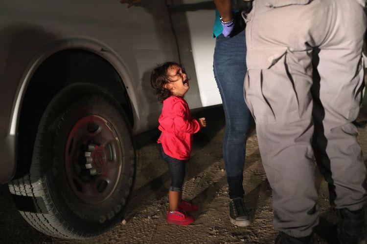 Yanela, bocah dua tahun asal Honduras, menangis di depan petugas perbatasan AS-Meksiko. Karena foto ini, dia menjadi ikon kebijakan imigrasi Presiden Donald Trump yang memisahkan migran anak dari orangtuanya.