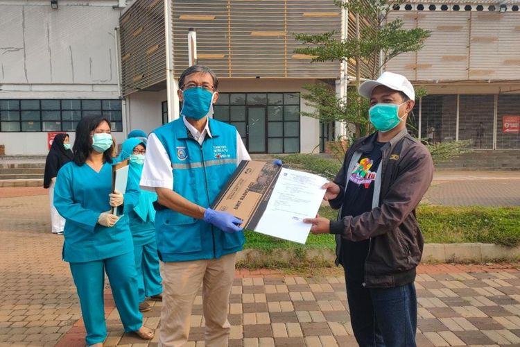 Yusuf Wibisono (kanan) salah seorang pasien sembuh Covid-19 bersama Tim Gugus Tugas Covid-19 Tangerang Selatan saat prosesi pemulangan di Rumah Lawan Covid-19, Selasa (14/7/2020)