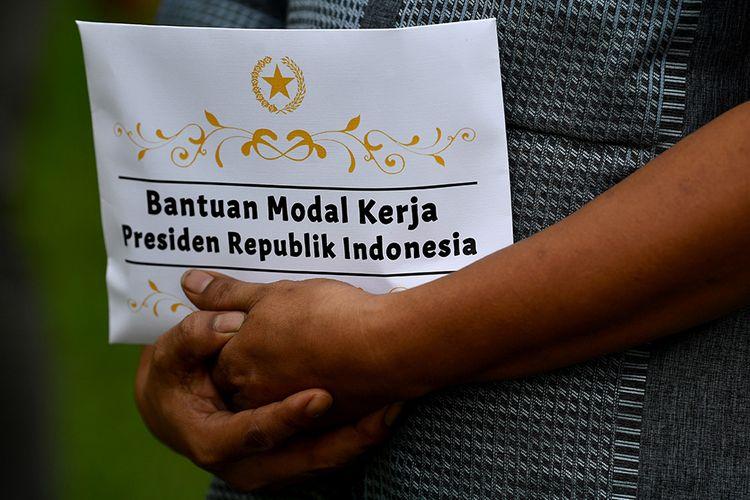 Seorang warga menerima bantuan modal kerja dari Presiden Joko Widodo di halaman tengah Istana Merdeka, Jakarta, Senin (13/7/2020). Presiden menyerahkan bantuan kepada 60 orang pengusaha mikro dan kecil masing-masing Rp2,4 juta sebagai tambahan modal kerja di tengah kondisi pandemi sehingga omzet dagangannya diharapkan akan lebih baik. ANTARA FOTO/Sigid Kurniawan/POOL/pras.