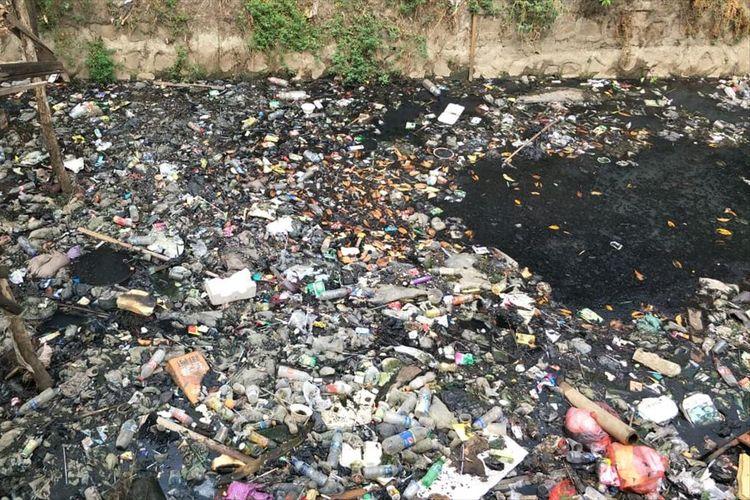 Tampak sampah plastik dan kemasan makanan memenuhi Kali Tegal Amba, Jakarta Timur, Selasa (9/7/2019).