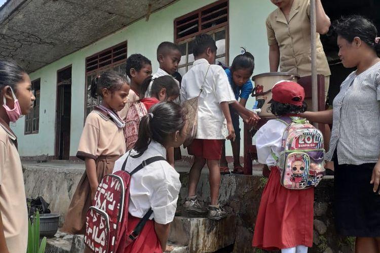 Foto : Siswa-siswi dan guru SDI Tuanio SDI) Tuanio, Desa Pagomogo, Kecamatan Nangaroro, Kabupaten Nagekeo, Flores, NTT, sedang mencuci tangan di kran air yang barus saja terpasang, Kamis (8/10/2020).