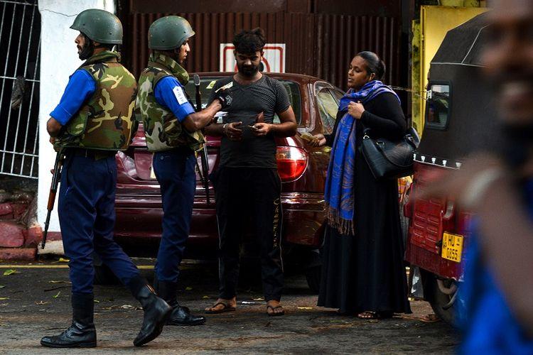 Seorang perempuan Muslim Sri Lanka (kanan) menjalani pemeriksaan aparat keamanan di Kolombo pada Rabu (30/4/2019). Tragedi bom Minggu Paskah yang disusul larangan mengenakan cadar membuat para perempuan Muslim negeri itu terpaksa menanggalkan hijab, cadar, atau abaya yang biasa mereka kenakan.