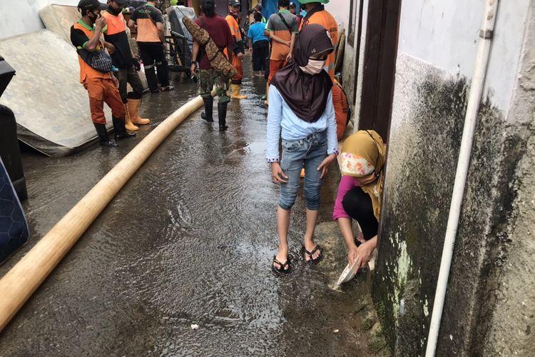 Sejumlah warga Jalan Damai 2 RT 04/RW 012, Ciganjur, Jagakarsa, Jakarta mulai membersihkan perabotan rumah tangga yang kotor karena terendam air dan lumpur pascabanjir akibat longsornya turap milik perumahan Melati Residence pada Senin (12/10/2020) siang.
